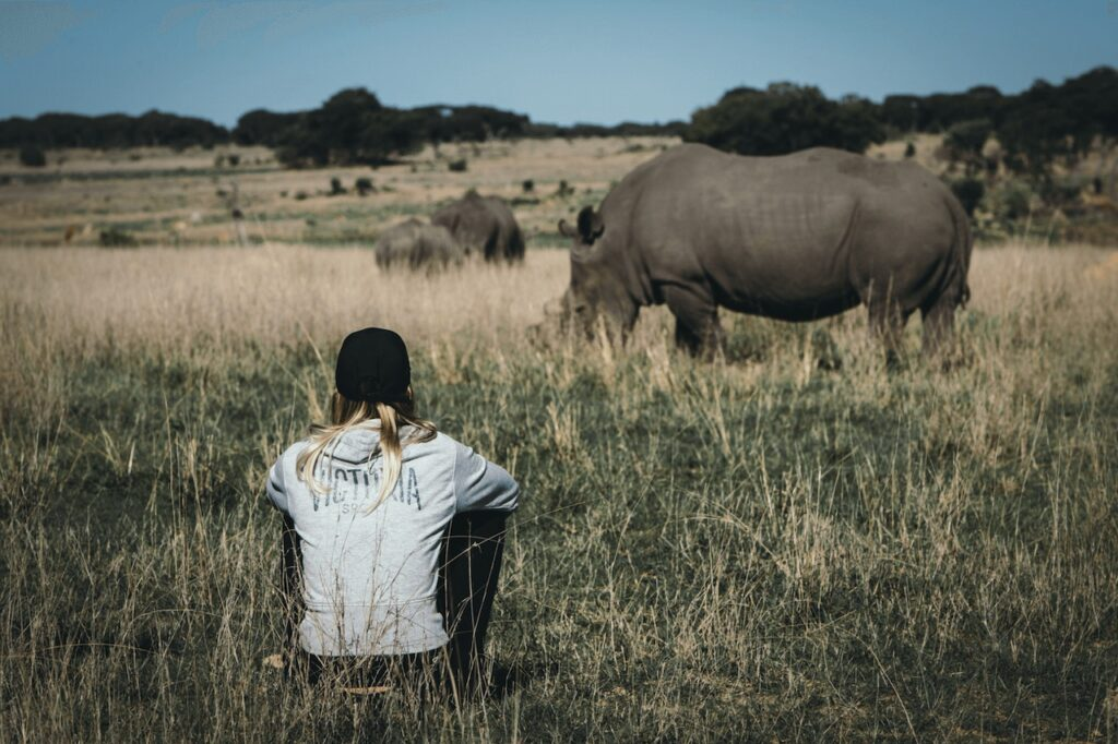 Volunteer in Zimbabwe sitting on ground with black rhino in the background