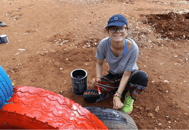 Volunteer painting childrens playground equipment