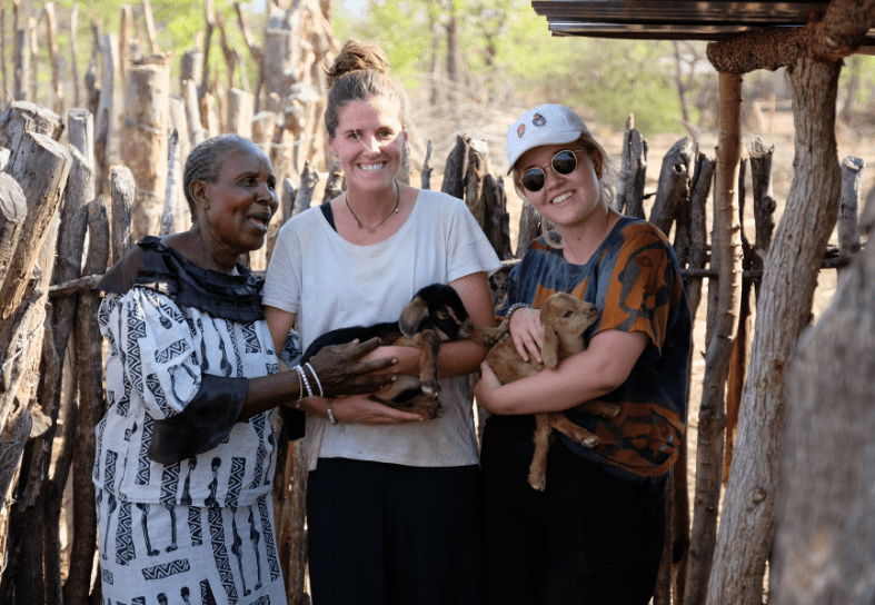 Two volunteers and local lady with a goat