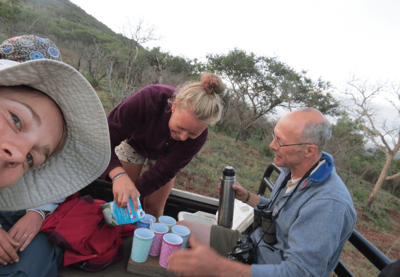 Three volunteers making tea in the bush