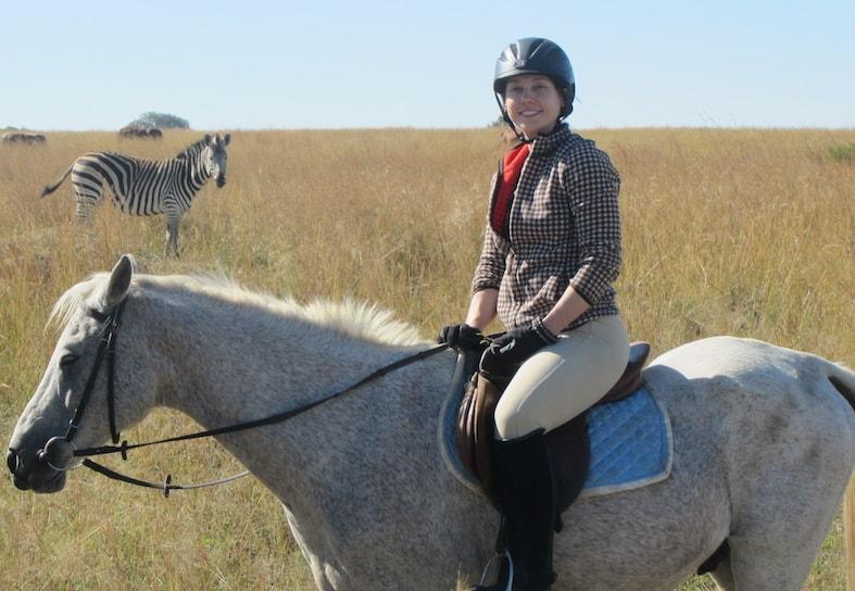 Horse riding volunteer with zebra