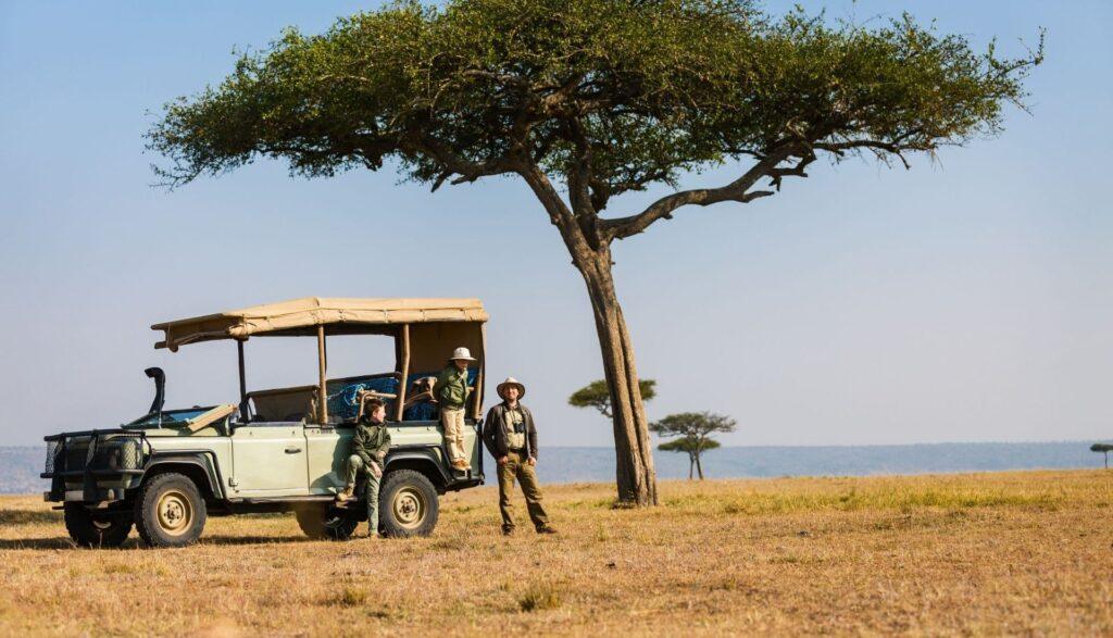 Volunteers standing by safari vehicle under tree in Africa