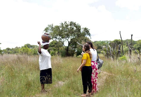 Two girls being taught to carry a bucket of water on their heads by a local African lady