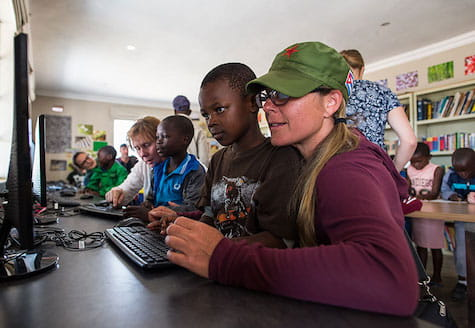 Girl volunteer helping young African child with computer work