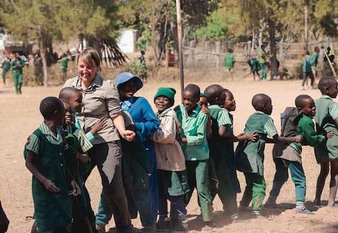 Older volunteer dancing with African schoolchildren