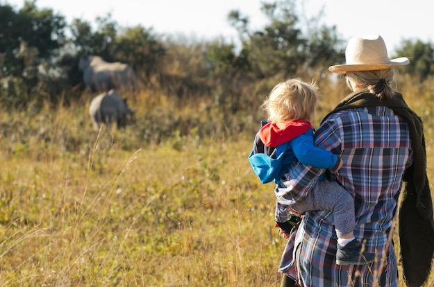 Mother and child watching a rhino in the bush