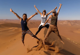 Group of volunteers jumping up on top of a sand dune